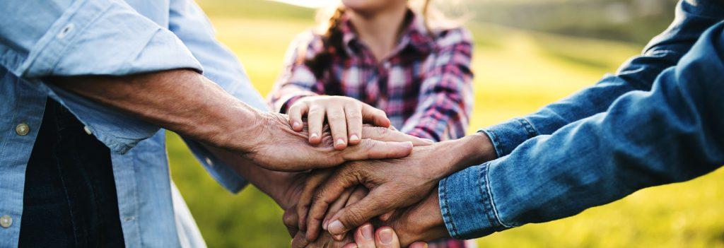 Kolmen henkilön kädet ovat yhdessä päällekkäin.