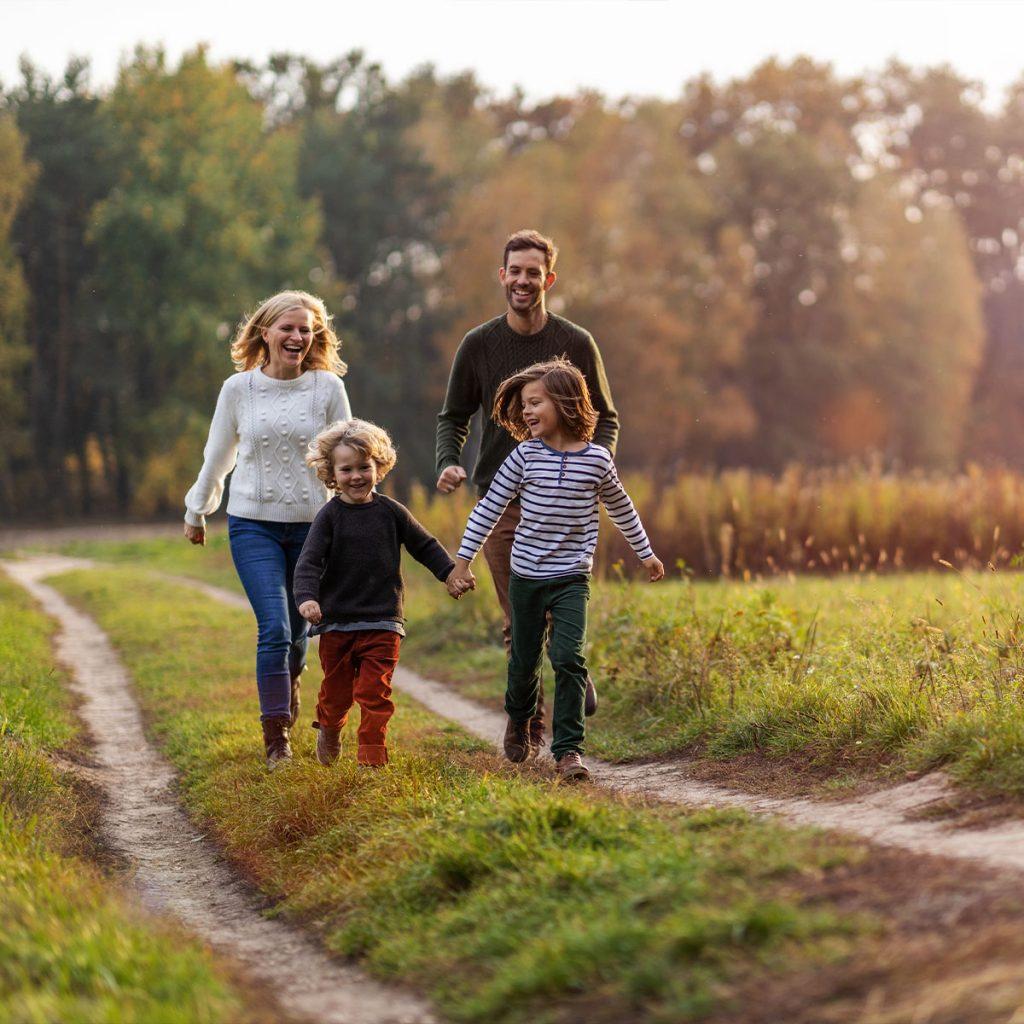 Kuvassa perhe kävelee polulla syksyisessä maisemassa.